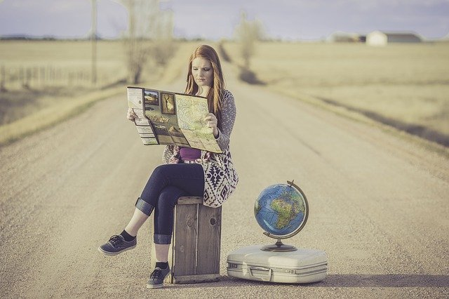 traveling girl reading map on side of road