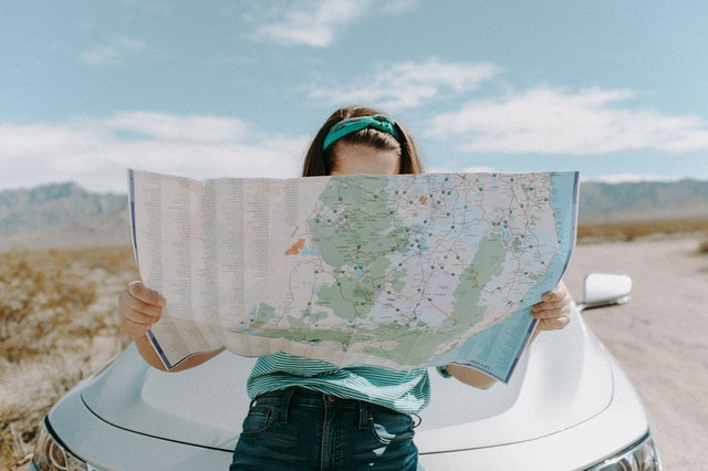 woman reading map on a road trip